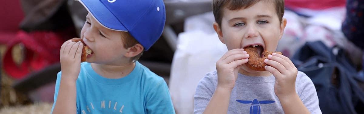 Boys devour apple cake donuts at Ciderfest