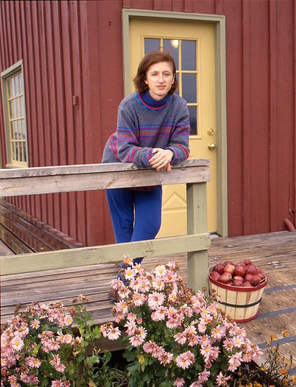 Shelly outside finished barn with apples